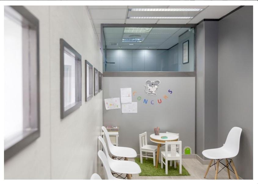 clínica dental en terrassa. sala de espera con sillas y mesa para niños con pinturas y papel para dibujar